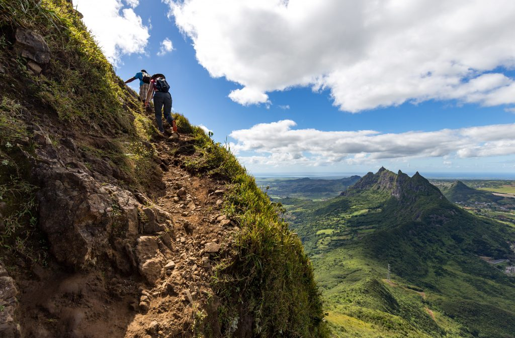 Two Persons Climbing Up The Trail To The Peak Of The Mountain Le Pouce On The Island Of Mauritius With A View Over Pieter Both.